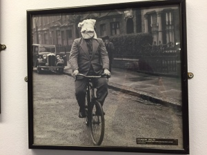 Man trying to ride a bicycle with his head bandaged up.